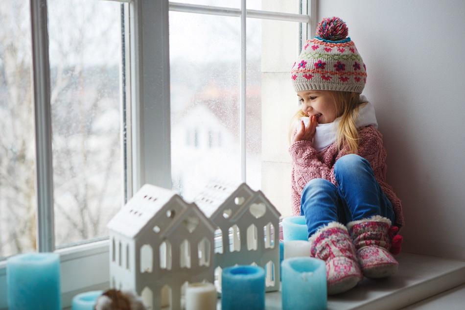 kid sitting in window looking at snow.jpg